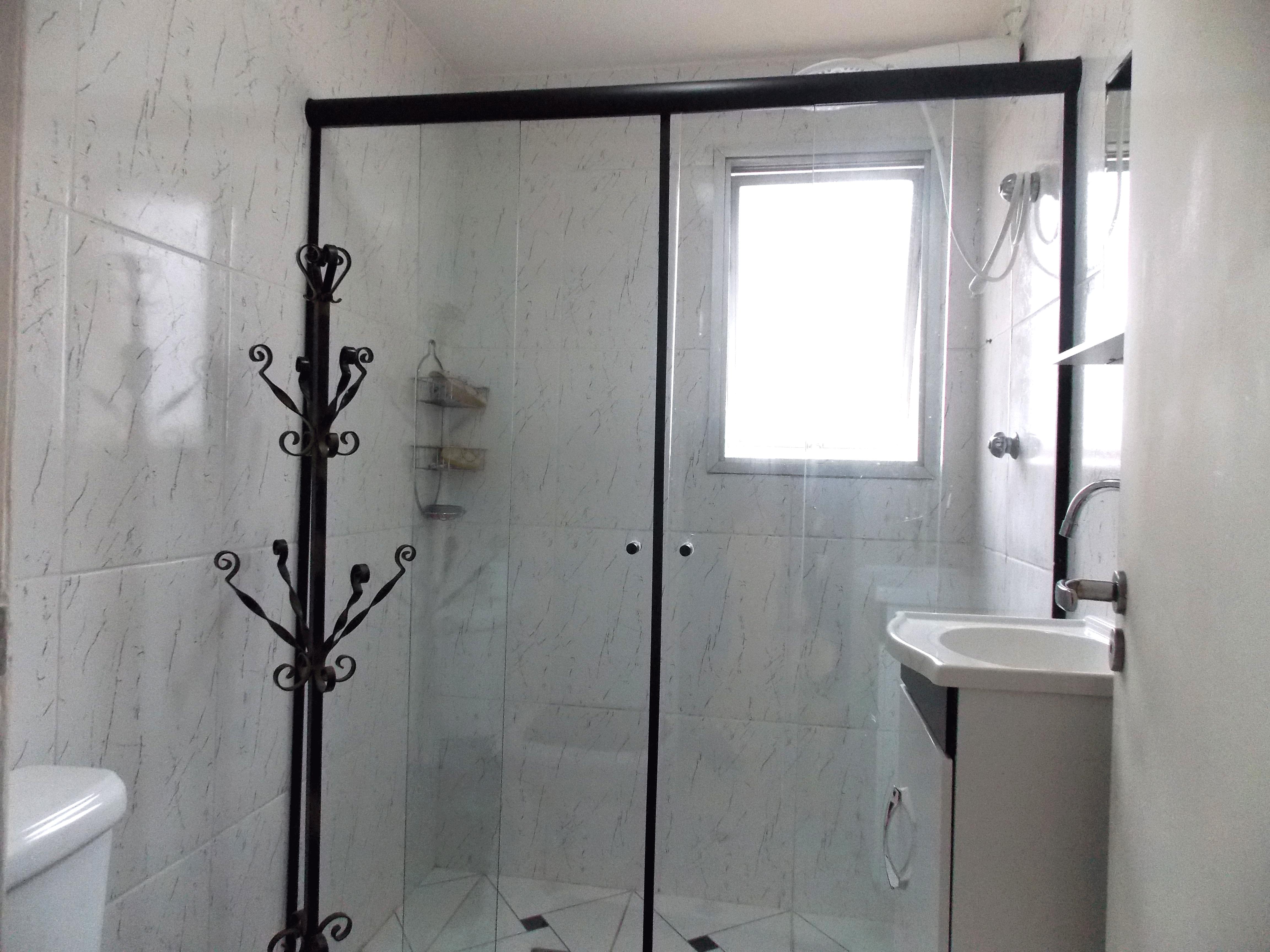 Jabaquara, Apartamento Padrão-Banheiro social com piso de cerâmica, pia de porcelana, gabinete, box de vidro e teto com moldura de gesso.
