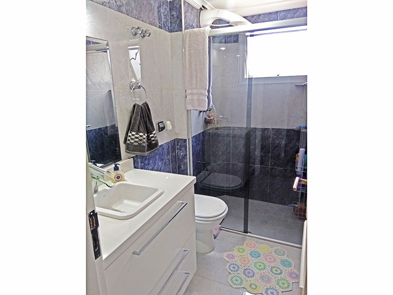 Jabaquara, Apartamento Padrão-Banheiro da suíte com piso de porcelanato, teto com moldura de gesso, gabinete, pia de porcelana e box de vidro.