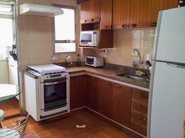 Jabaquara, Apartamento Padrão-Cozinha ampla com piso de cerâmica, armários, pia de granito e porta de vidro na passagem para área de serviço