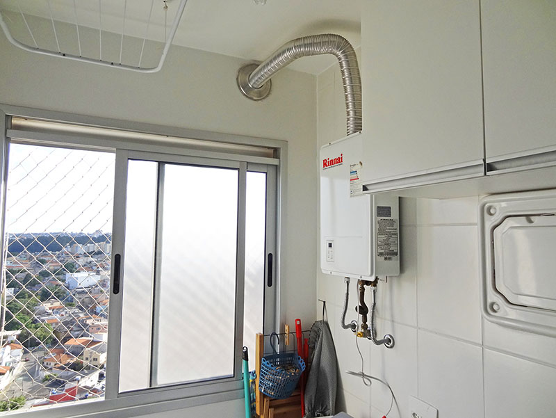 Sacomã, Apartamento Padrão-Área de serviço com piso de cerâmica, armários, aquecedor de passagem e janela com tela de proteção.