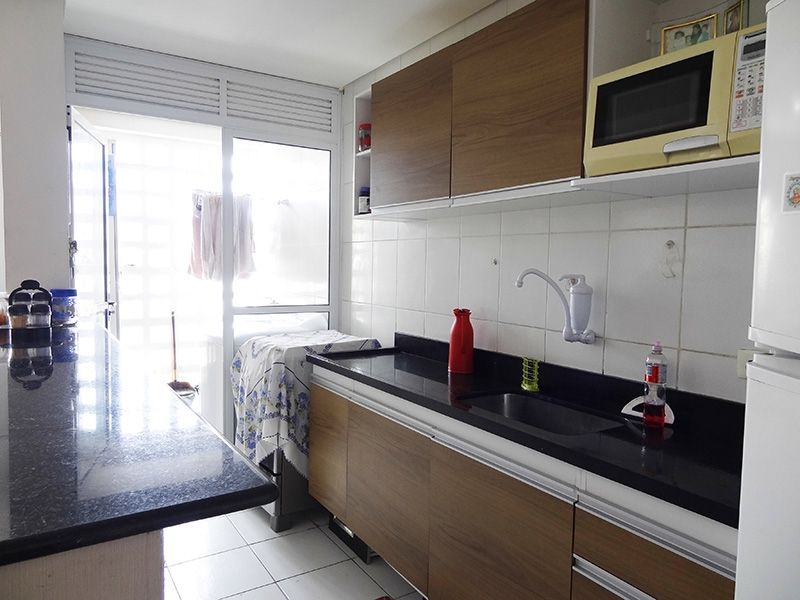 Jabaquara, Apartamento Padrão-Cozinha americana com piso de cerâmica, pia de granito com gabinete, armários e porta de vidro na passagem para a área de serviço.