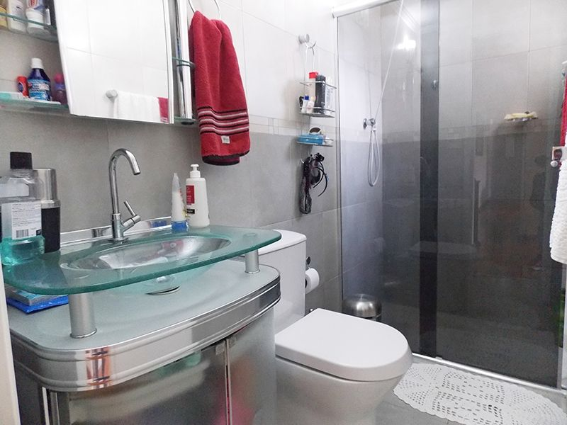 Jabaquara, Apartamento Padrão-Banheiro social com piso de cerâmica, teto com moldura de gesso, pia de vidro com gabinete e box de vidro.