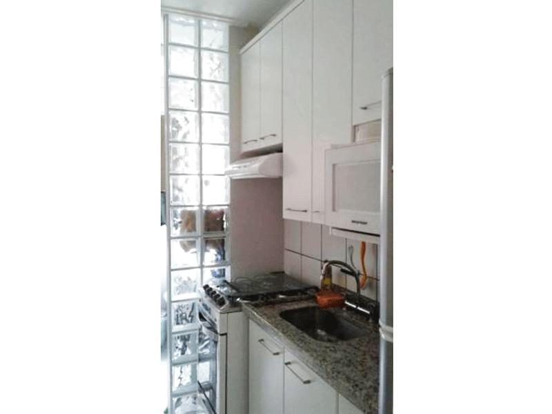 Jabaquara, Apartamento Padrão-Cozinha com piso de cerâmica, pia de granito com gabinete, armários planejados e parede de vidro na passagem para a área de serviço.