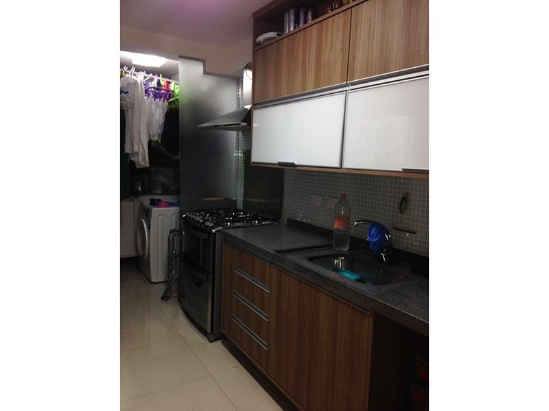 Jabaquara, Apartamento Padrão-Cozinha com piso de porcelanato,  pia de granito com gabinete, armários e porta de vidro na passagem para a área de serviço.