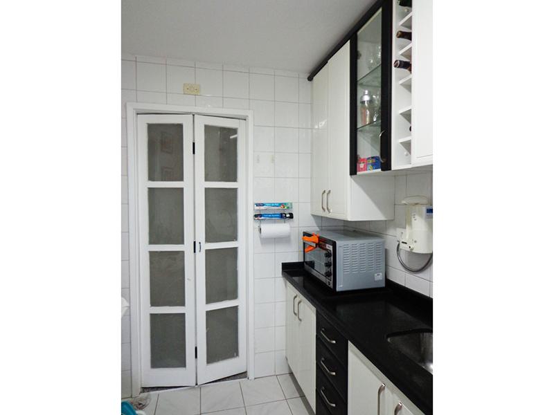 Jabaquara, Apartamento Padrão-Cozinha com piso de cerâmica, pia de granito com gabinete, armários e porta de vidro na passagem para a área de serviço.