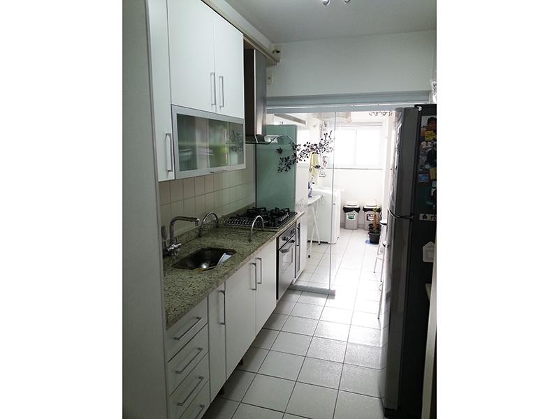 Ipiranga, Apartamento Padrão-Cozinha com piso de cerâmica, pia de granito com gabinete, armários planejados e porta de vidro na passagem para área de serviço.
