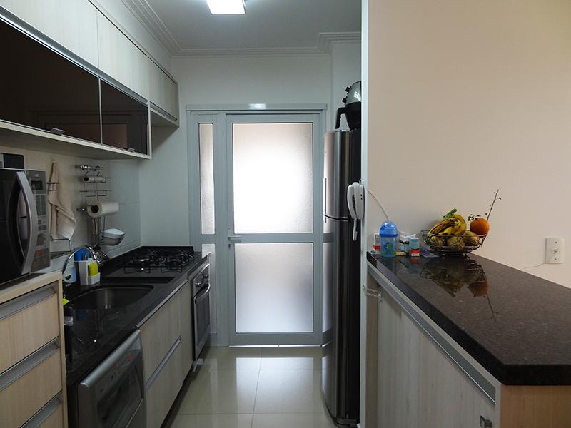 Ipiranga, Apartamento Padrão-Cozinha americana com piso de porcelanato, teto com moldura de gesso, pia de granito com gabinete, armários planejados e porta de vidro na passagem para a área de serviço.