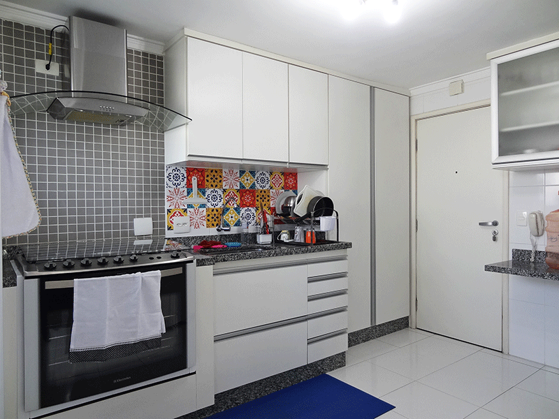 Ipiranga, Apartamento Padrão-Cozinha com piso de cerâmica, pia de granito, gabinete, armários planejados, coifa, teto com moldura de gesso e porta de madeira na passagem para a área de serviço.