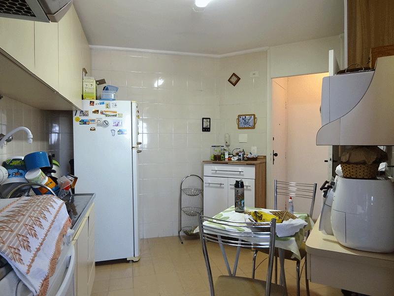 Jabaquara, Apartamento Padrão-Cozinha com piso de cerâmica, pia de inox, gabinete, armários planejados, teto com moldura de gesso e porta de vidro na passagem para a área de serviço.