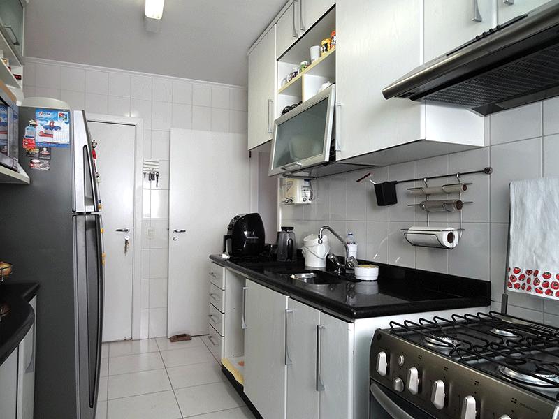 Ipiranga, Apartamento Padrão-Cozinha com piso de cerâmica, pia de granito, armários planejados, teto com moldura de gesso e porta de vidro na passagem para a área de serviço.