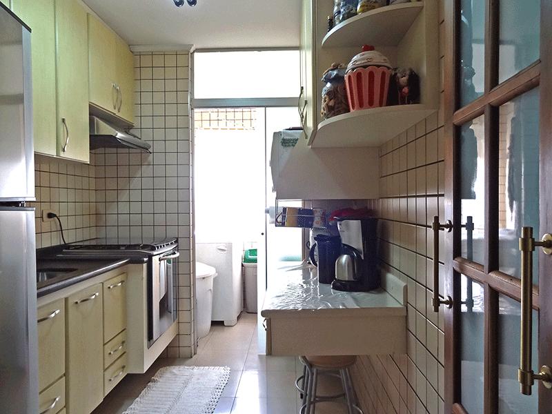 Sacomã, Apartamento Padrão-Cozinha com piso de porcelanato, pia de granito, gabinete, armários planejados, teto com moldura de gesso e porta de vidro na passagem para a área de serviço.