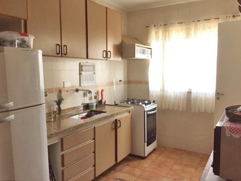 Ipiranga, Apartamento Padrão-Cozinha com piso de cerâmica, pia de granito, gabinete, armários planejados, teto com moldura de gesso e porta de madeira na passagem para a área de serviço.