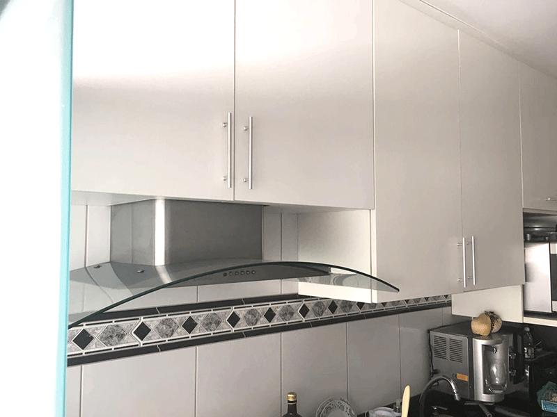 Jabaquara, Apartamento Padrão-Cozinha com piso de porcelanato, pia de granito, gabinete, coifa, armários planejados e porta de vidro na passagem para a área de serviço.