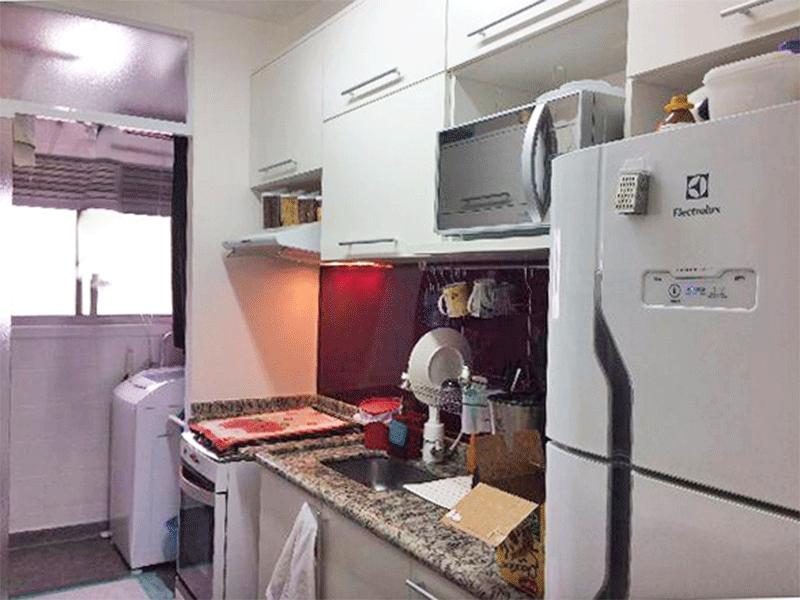 Ipiranga, Apartamento Padrão-Cozinha com pia de granito, gabinete, armários planejados e porta de vidro na passagem para a área de serviço.