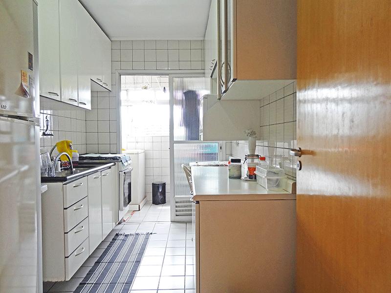 Jabaquara, Apartamento Padrão-Cozinha piso cerâmica, pia de granito, armários planejados, teto com moldura de gesso e porta de vidro na passagem para a área de serviço.