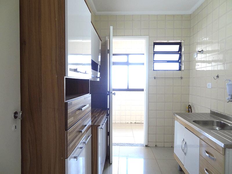 Jabaquara, Cobertura Duplex-Cozinha com piso de porcelanato, pia de inox, gabinete, teto com moldura de gesso e porta de madeira na passagem para a área de serviço.