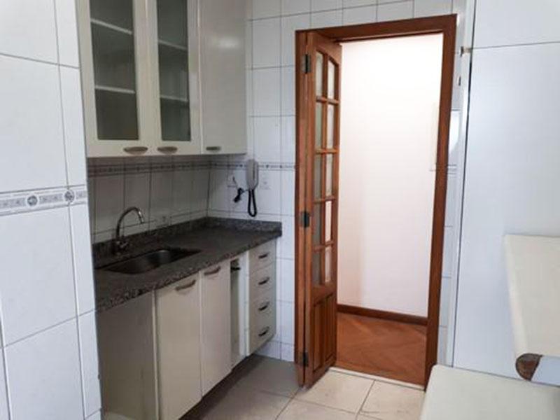 Sacomã, Apartamento Padrão-Cozinha com piso de cerâmica, pia de granito com gabinete, armários planejados e porta de vidro na passagem para a área de serviço.